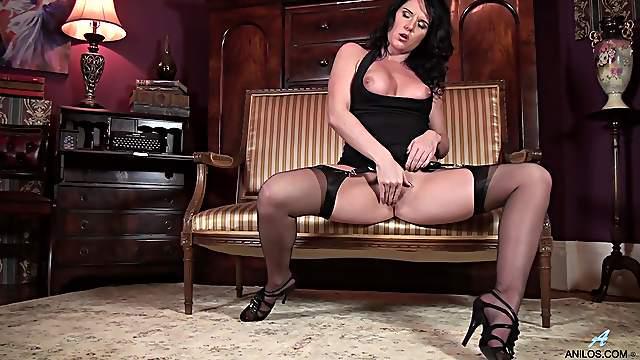 Mature slut Leah moans while pleasuring her pussy on a sofa
