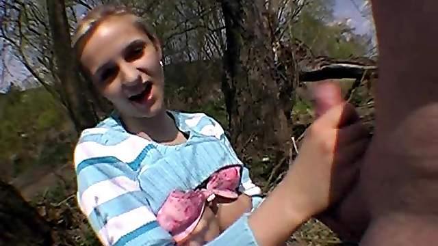 Czech teen fondling her natural tits while giving a handjob outdoors