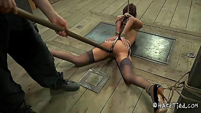 Crucified bondage slave yelling when tortured in BDSM