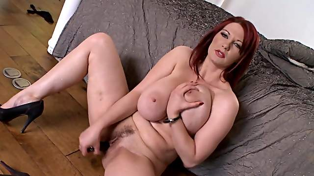 Busty redhead playing with toys