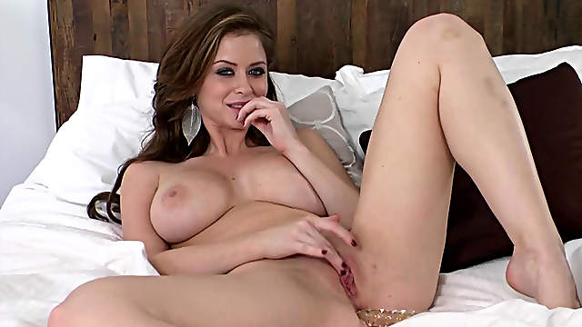 Long-haired beauty with big boobs drills herself with a dildo